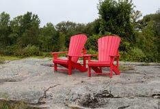 在花岗岩小山的两把红色椅子 库存图片
