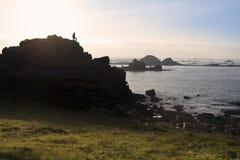 在花岗岩岩石顶部的人剪影 免版税图库摄影