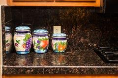 在花岗岩柜台的三个厨房装饰容器 免版税库存图片