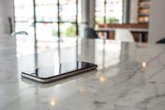 在花岗岩桌上的手机在被弄脏的咖啡馆 图库摄影