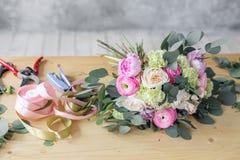 在花店的工作表 女孩助理或所有者在花卉设计演播室,做装饰和安排 库存照片