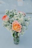 在花束的玫瑰色的桔子和雏菊在玻璃投入了 免版税图库摄影