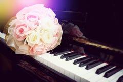 在花束的罗斯花在钢琴键盘与轻的火光的 免版税库存图片