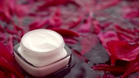 在花瓣和水背景,皮肤的自然科学的敏感skincare润肤霜面霜 股票录像