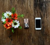 在花瓶、照相机和电话的花在老木桌上 免版税库存图片