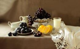 在花瓶、花和柠檬的成熟葡萄 免版税库存照片