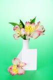 在花瓶和一张空的卡片的桃红色德国锥脚形酒杯 免版税库存照片