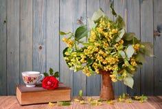 在花瓶和书的菩提树花 免版税库存图片