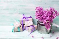 在花瓶和箱子的紫罗兰色淡紫色花有礼物的 库存照片