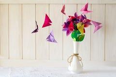 在花瓶和蝴蝶的Origami纸花在白色木墙壁上 图库摄影