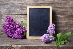 在花瓶和黑板的淡紫色花 免版税库存图片