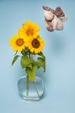在花瓶的三个向日葵用水 猫飞行物 免版税库存图片