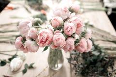 在花瓶的桃红色牡丹在木地板和bokeh背景-减速火箭的被称呼的照片上 软绵绵地集中 库存照片