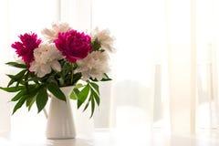 在花瓶的白色和桃红色牡丹在白色桌上 免版税库存图片
