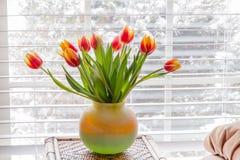 在花瓶的美丽的郁金香在窗口附近的桌上 免版税库存图片