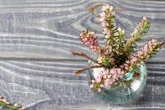 在花瓶的花在木背景 免版税库存照片