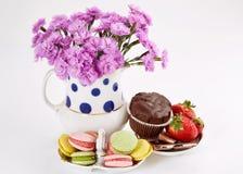 在花瓶的花用在茶碟的蛋白杏仁饼干 康乃馨和甜点 免版税图库摄影