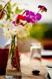 在花瓶的香豌豆花在与花的宴会桌设置在庭院露台餐馆 免版税库存照片