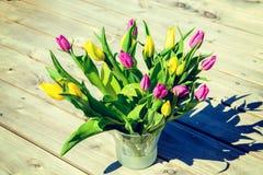 在花瓶的黄色和紫罗兰色郁金香在木地面 库存照片