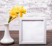 在花瓶的黄色花和倒空白色框架 免版税库存图片