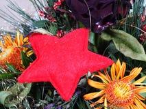 在花的布置的红色星 免版税库存图片