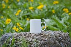 在花的领域的一个空白的加奶咖啡杯子 免版税库存图片