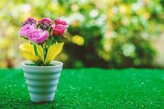 在花盆的人造花在绿草 免版税库存图片