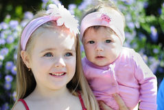 在花附近的两个美丽的女孩 图库摄影