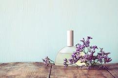 在芳香花旁边的新鲜的葡萄酒香水瓶在木桌上 减速火箭的被过滤的图象 库存图片