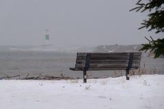 在苏必利尔湖畔积雪的岸的公园长椅  库存图片
