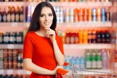 在苏打和刷新的饮料架子前面的微笑的妇女 免版税图库摄影