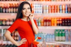 在苏打和刷新的饮料架子前面的微笑的妇女 图库摄影