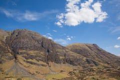 在苏格兰山的白色云彩在有阳光Glencoe苏格兰英国惊人的美丽的苏格兰幽谷的春天在Lochaber 库存照片