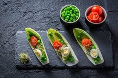 在苦苣生茯的健康沙拉用鲕梨、芦笋和豌豆 免版税图库摄影