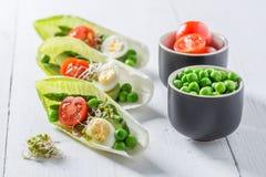 在苦苣生茯的创造性的沙拉用鲕梨、芦笋和豌豆 库存照片