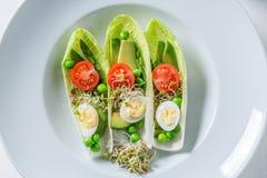 在苦苣生茯的新鲜的沙拉用鲕梨、芦笋和豌豆 免版税库存照片
