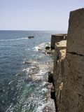 在英亩以色列城市的城市墙壁的前面小船 库存图片