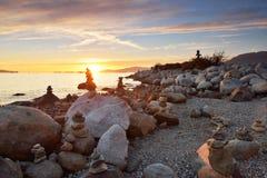 在英吉利湾的平衡的岩石雕塑在日落期间 免版税库存照片