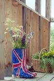 在英国国旗橡胶起动wellies的野花 库存照片