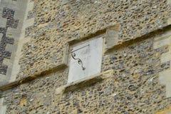 在英国晒黑在中世纪教区教堂墙壁上的拨号盘  库存图片