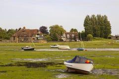 在英国的南部的西萨塞克斯郡打开小船被着陆低潮中在历史的港口在Bosham 免版税图库摄影