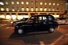 在英国` s首都街道上的典型的伦敦出租汽车  免版税图库摄影