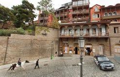 在英王乔治一世至三世时期首都历史街道上的马车手有被修补的石头和老房子的 免版税图库摄影