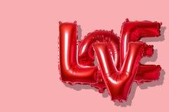 在英语字母表的词爱从在明亮的背景的红色气球 最小的爱概念 免版税库存照片