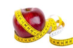 在苹果减重附近被包裹的测量的磁带 免版税图库摄影