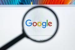 在苹果计算机iMac显示器屏幕上的谷歌主页在放大镜下 谷歌是世界` s多数普遍的搜索引擎 免版税库存图片