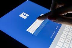在苹果计算机iPad的一个妇女` s手触摸屏赞成在与Facebook主页网页的晚上 Facebook最大的社会网络 免版税库存图片