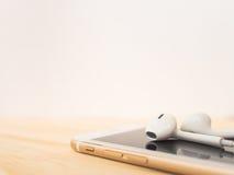 在苹果计算机iPhone顶部的苹果计算机EarPods 库存图片
