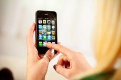 在苹果计算机iPhone 4的妇女访问的家庭屏幕 免版税库存照片