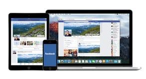 在苹果计算机iPhone iPad和Macbook赞成显示的Facebook app 库存图片